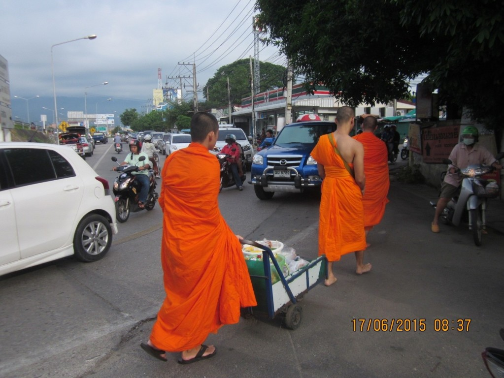 Monks bearing alms in the morning with no pavement to walk on.